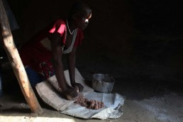 Martha grinds sorghum in her neighbour's compound in South Sudan, during the 2017 famine in East Africa