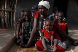 Martha sits with her four children in her neighbour's compound in South Sudan, during the 2017 famine in East Africa.