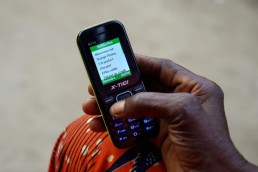 Yvette shows how she uses Mobile Money on her phone in Ivory Coast
