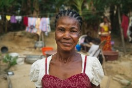 Yvette smiles outside her home in Ivory Coast, as she explains how Mobile Money has improved her life