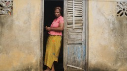 Elyse uses mobile money on her phone at her home in Ivory Coast