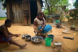 Elyse cooks outside her home in Ivory Coast as she explains how she uses Mobile Money