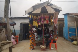 Katy waits for customers outside her stall in Ivory Coast as she explains how Mobile Money has improved her life