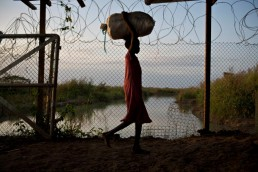 A girl carries her family's possessions into a Protection of Civilians Camp in South Sudan