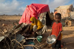 A family stands outside their tent in a camp in a drought ravaged area of Somalia