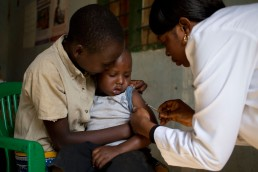 A health worker with GAVI vaccinates a . young boy being held by his brother against measles and rubella in Tanzania