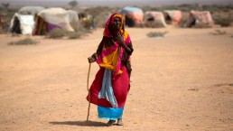 An older woman walks in a camp for displaced people in a drought ravaged area of Somalia