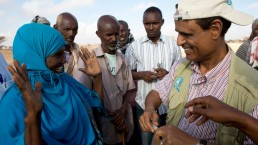 An FAO staff member shows Dhux how to protect her livestock against disease in a drought ravaged area of Somalia