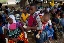 Children wait to be vaccinated against measles and rubella with GAVI in Tanzania