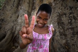 Nine-year old Monique shows a vaccination sign as she waits for a measles and rubella vaccination from GAVI in Tanzania