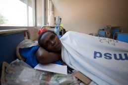 Kitmonga, who suffers from cervical cancer, lies in a hospital bed with Tanzania