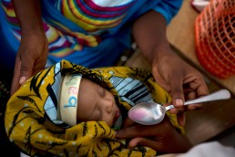 A baby is fed cough medicine after displaying measles symptoms in Tanzania
