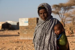A mother and child stand in the drought ravaged village of Qardho, Somalia