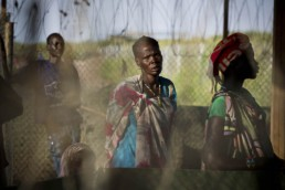 Familes wait outside the gates of a UN Protection of Civilians Camp in South Sudan