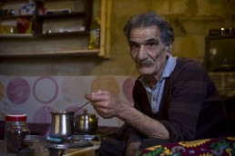 An elderly Syrian refugee makes coffee in Lebanon