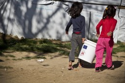 Young Syrian refugee girls carry a bucket in Lebanon