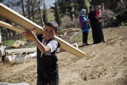 A young Syrian refugee boy carries a plank of wood in Lebanon
