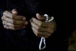 An elderly Syrian refugee prays in Lebanon