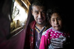 A Syrian refugee poses for a photo with his disabled daughter in Lebanon
