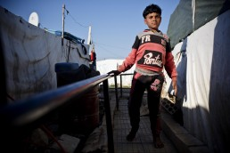 A disabled Syrian refugee boy walks with the help of a rail in Lebanon