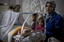 A Syrian refugee watches over her baby in Lebanon