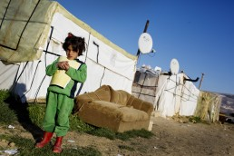 A Syrian refugee girl holds a book in Lebanon
